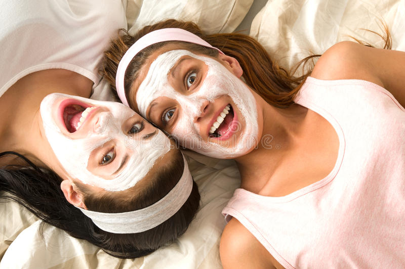 Crazy girls with facial mask lying bed royalty free stock image