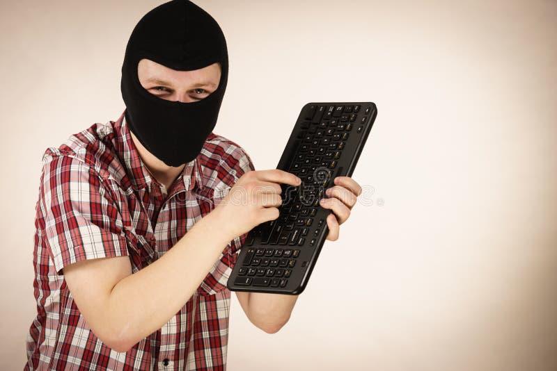 Man wearing balaclava holding keyboard stock photo