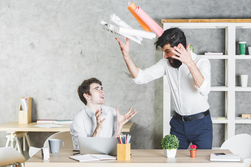 Crazy handsome colleagues in office stock image