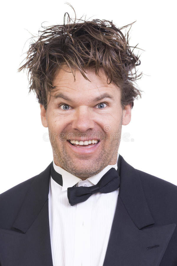 Crazy high man in tuxedo. Portrait of high Caucasian man with crazy facial expression and messy long hair on white background stock image