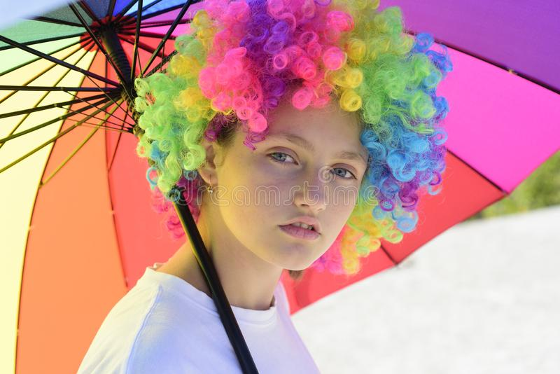Crazy hipster girl. fashion girl with colorful hair wig and umbrella. kid in summer camp. happy youth party. autumn royalty free stock image