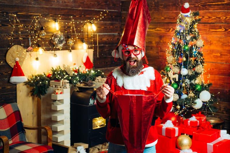 Crazy Hipster Santa with shopping bag at home. Christmas preparation - man celebrating New Year. Bearded modern Santa royalty free stock photography