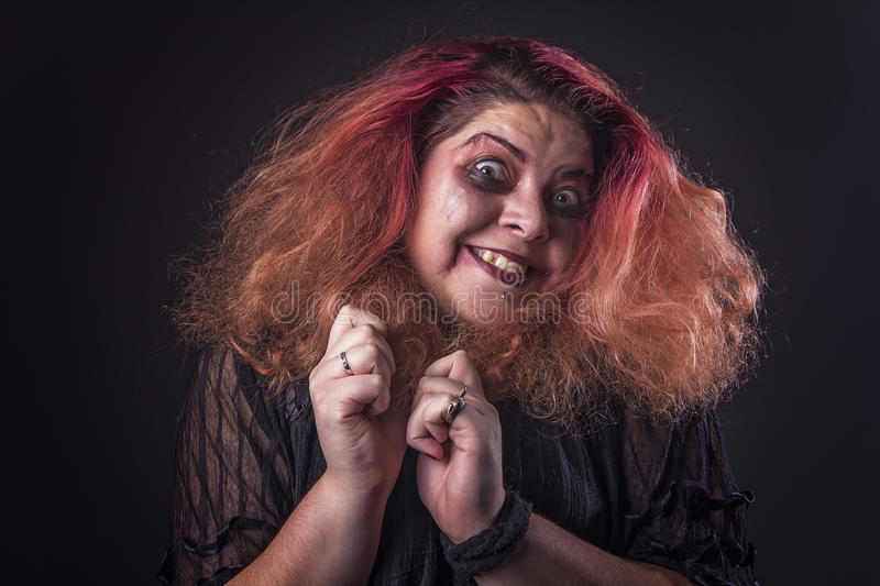 Crazy horror woman screaming. Deranged, mentally ill, scary girl laughing sinisterly stock photo