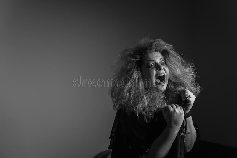 Crazy horror woman screaming. Mad, deranged girl screams loudly stock photo