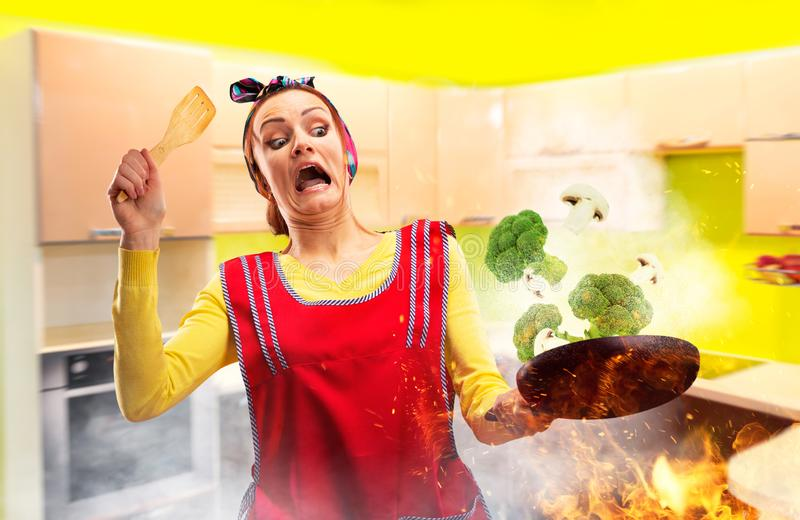 Crazy housewife in apron cooking broccoli on fire. Kitchen interior on background. Funny female person with a frying pan, work is not going according to plan stock image