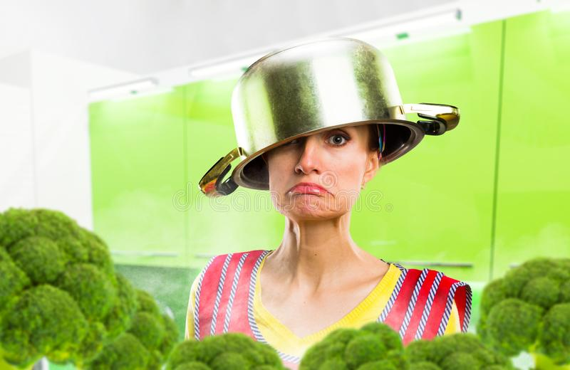 Crazy housewife in apron with a pot on her head royalty free stock photo