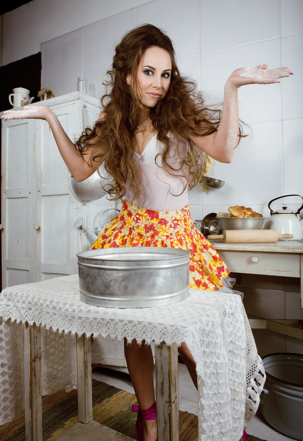 Crazy housewife on kitchen smiling eating cakes. Real interior stock photo