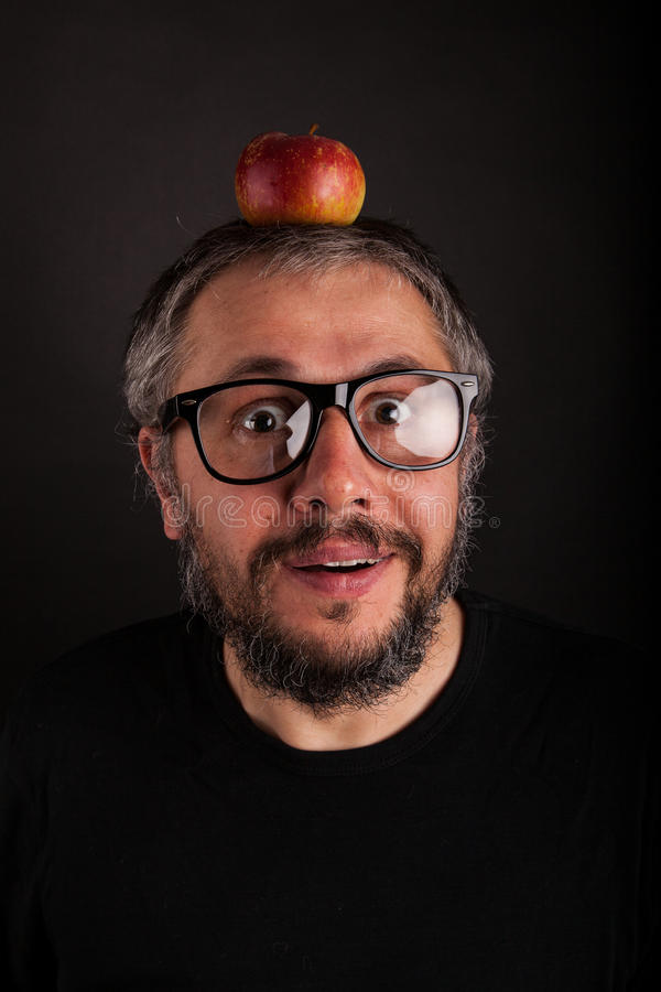 Crazy looking grumpy old man with grey beard and big nerd glasses with apple stock images
