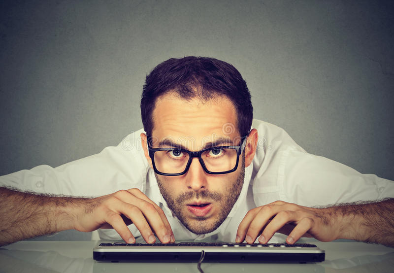 Crazy looking nerdy man typing on keyboard royalty free stock photo