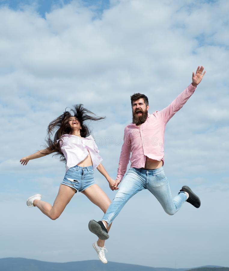 Crazy in love. Woman and man jump in cloudy sky. Enjoy carefree time together. Summer vacation. Feeling freedom. Playful. Crazy in love. Woman and men jump in stock photos