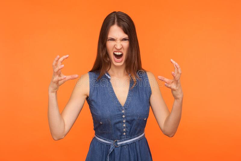 Crazy mad brunette woman in denim dress screaming angrily with furious enraged expression. Raising claws in aggression, experiencing strong emotions. indoor stock images