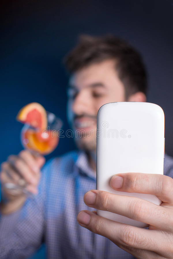 Crazy man making a selfie with a cocktail. At the party stock photos