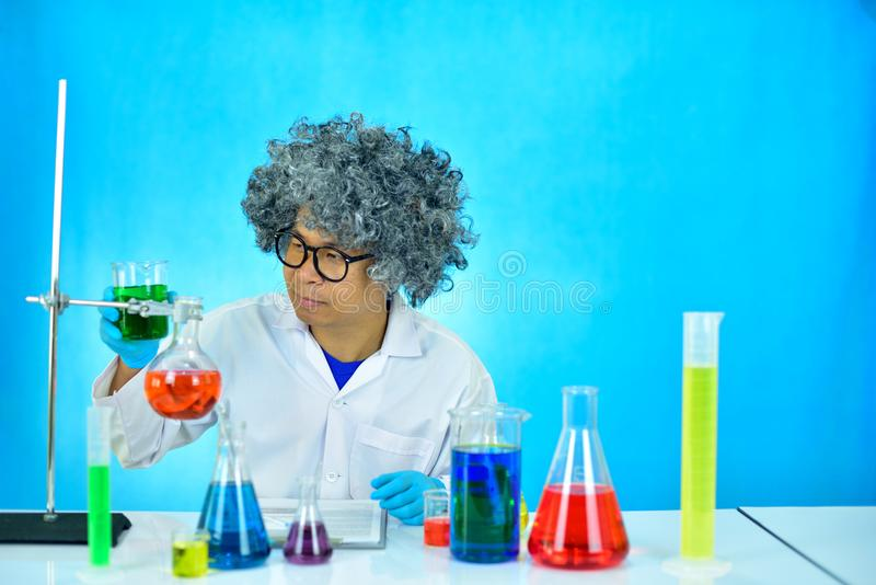 Crazy man scientist working with chemical in research laboratory, blue background royalty free stock photos
