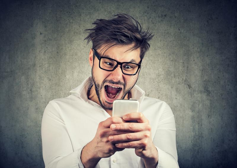 Super excited man watching smartphone stock photography