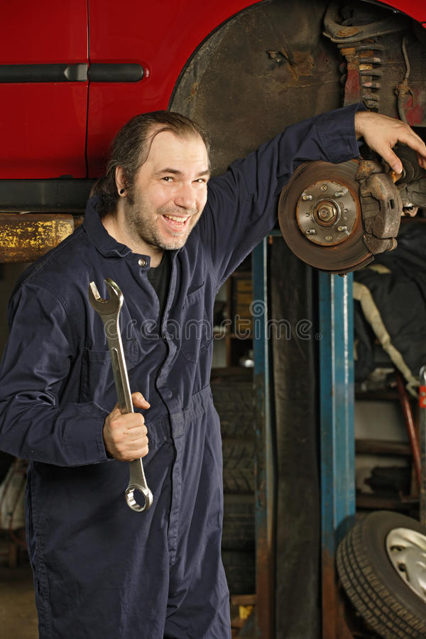 Crazy mechanic fixing the brakes. A crazy happy mechanic fixing brakes royalty free stock image
