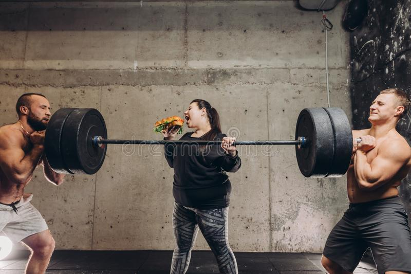 Crazy obese girl having breakfast while two sportsmen holding barbell. Close up photo stock photography