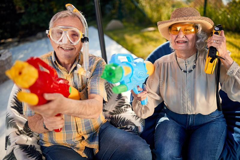 Crazy old people have fun on vacation playing with  water gun. Crazy old happy people have fun on vacation playing with  water gun royalty free stock photos