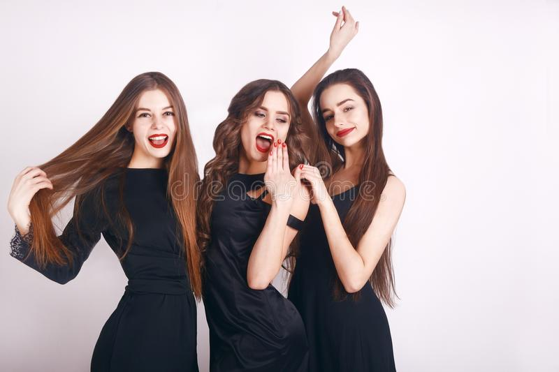 Crazy party time of three beautiful stylish women in elegant evening casual black dress celebrating , having fun, dancing. On white background. Best friends stock photography