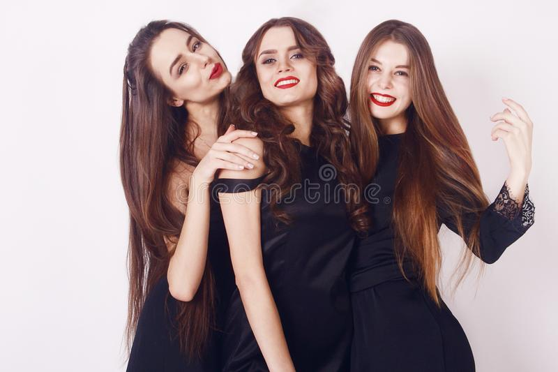 Crazy party time of three beautiful stylish women in elegant evening casual black dress celebrating , having fun, dancing. On white background. Best friends stock photo