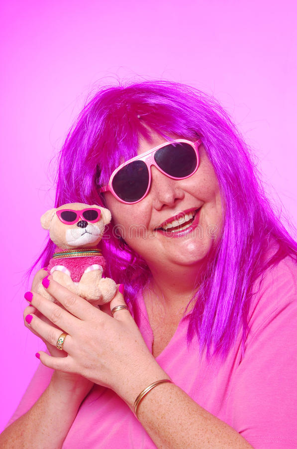 Crazy pink woman with teddy dog. Portrait of a Caucasian woman all in pink with sunglasses and dog teddy toy with happy smiling crazy facial expression. Image on stock photo