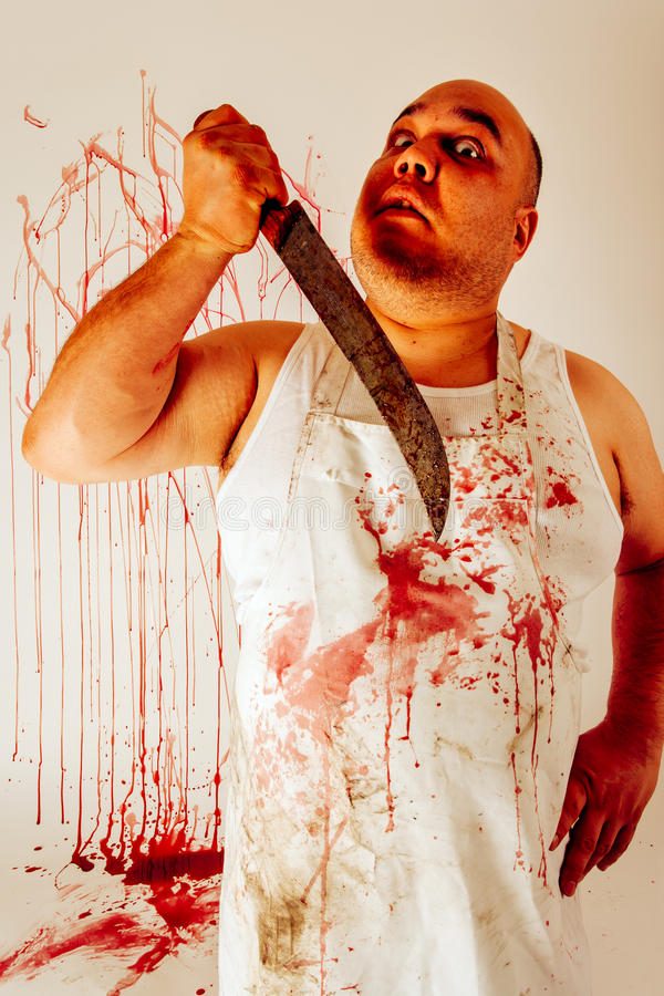Crazy psycho butcher. Crazy insane butcher covered with blood. Harsh lighting for more disturbing feel royalty free stock image