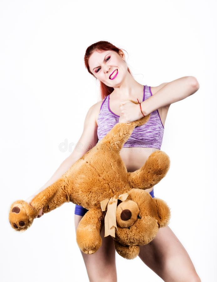 Crazy redhead young woman tears off a bears legs royalty free stock image