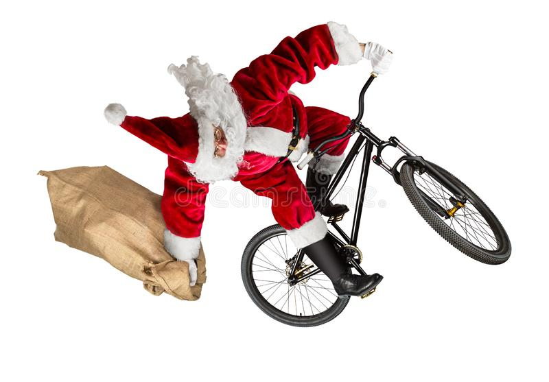 Crazy santa claus jump on dirt mountain bike with jute burlap ba. G isolated abstract christmas funny sport white background stock image