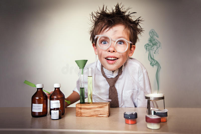 Crazy scientist. Young boy performing experiments royalty free stock images