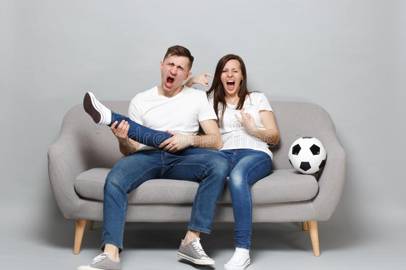 Crazy screaming couple woman man football fans cheer up support favorite team with soccer ball hold leg like guitar royalty free stock photo