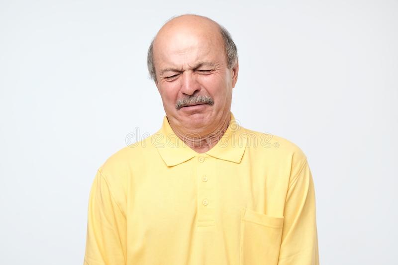 Crazy senior bald hispanic man crying receiving bad news. Negative facial emotion stock image