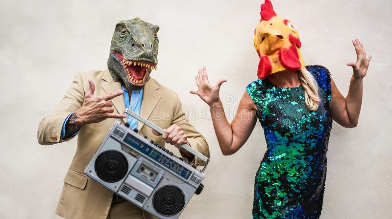 Crazy senior couple dancing at carnival party wearing t-rex and chicken mask - Old trendy people having fun listening music with. Boombox stereo - Absurd and stock photography