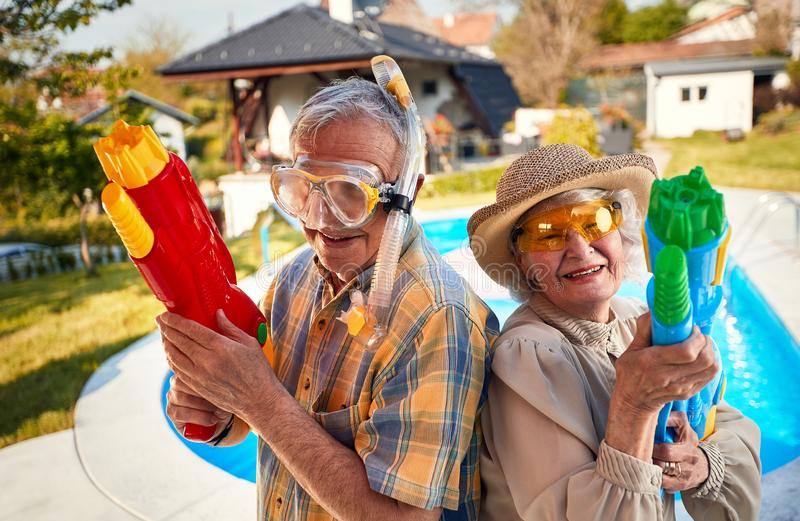Crazy senior people have fun on vacation playing with  water gun. Crazy senior happy people have fun on vacation playing with  water gun royalty free stock photo