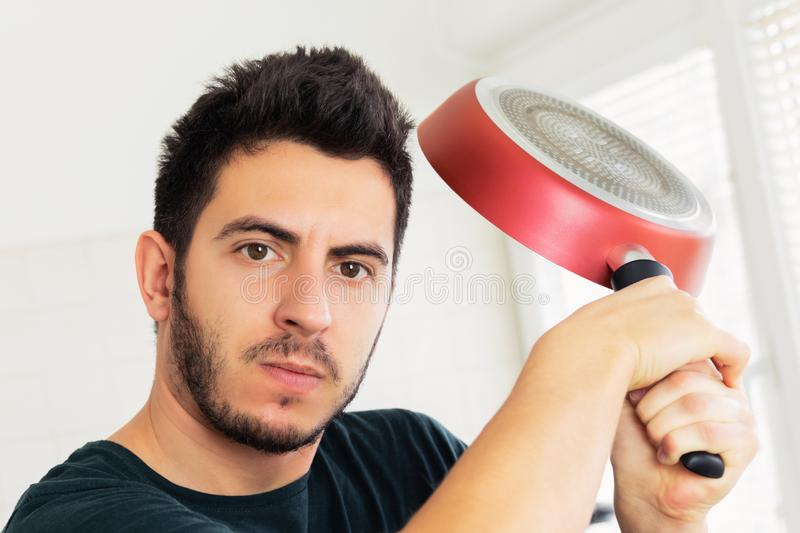 Crazy very angry young man threatening with frying pan. On the kitchen royalty free stock image