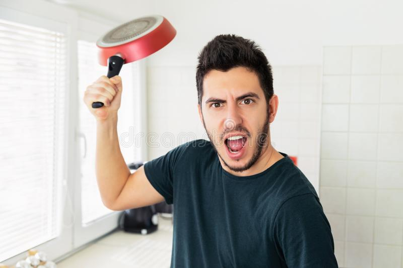 Crazy very angry young man threatening with frying pan. On the kitchen royalty free stock photo