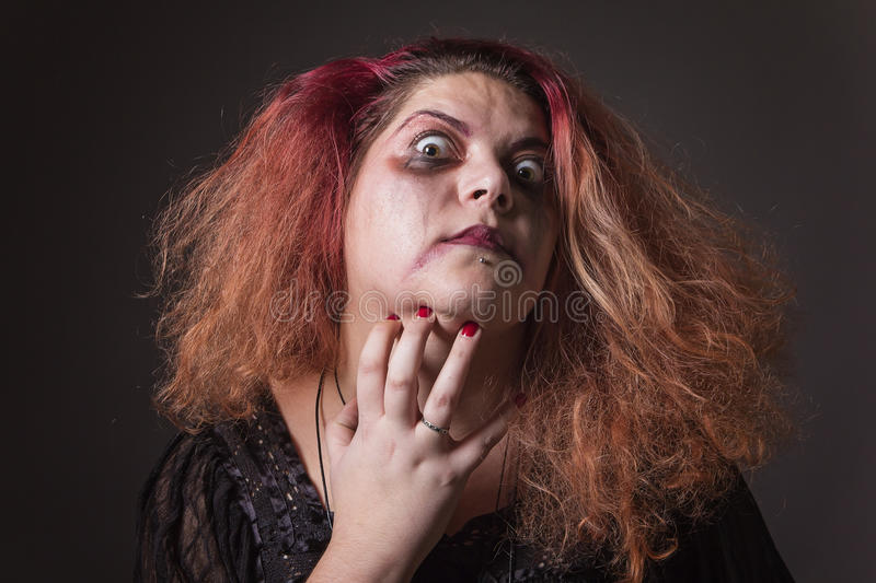 Crazy witch crawling her face. Possessed deranged young woman hurting her neck royalty free stock photo