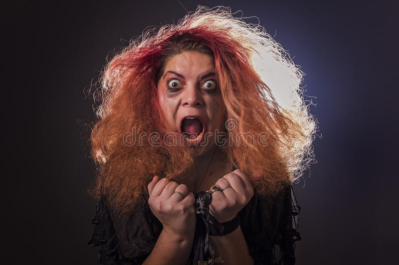 Crazy witch laughing histerically. Possessed deranged young woman screaming and laughing uncontrollably royalty free stock image