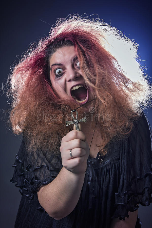 Crazy witch laughing histerically. Possessed deranged young woman screaming and laughing uncontrollably royalty free stock photography