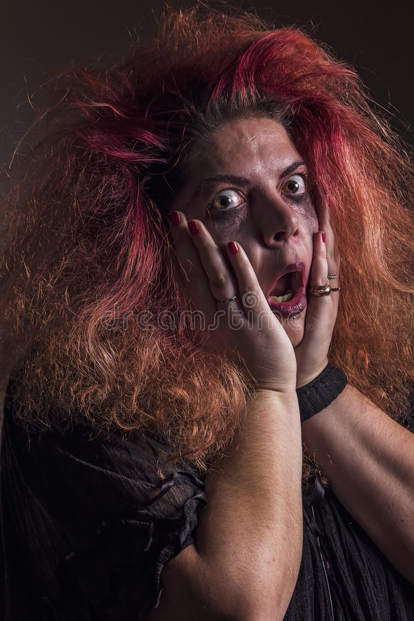 Crazy witch scared. Possessed deranged young woman is frightened royalty free stock image