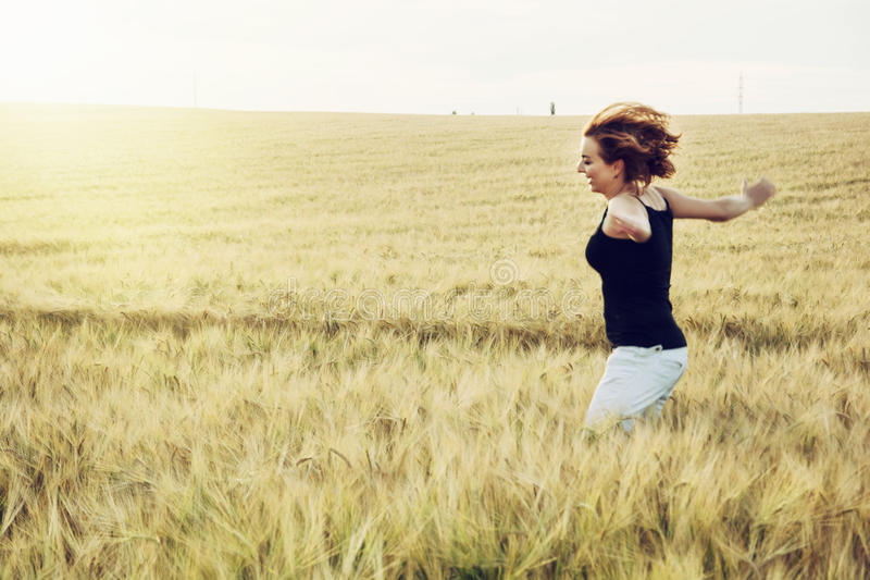Crazy woman is jumping in the wheat field stock image
