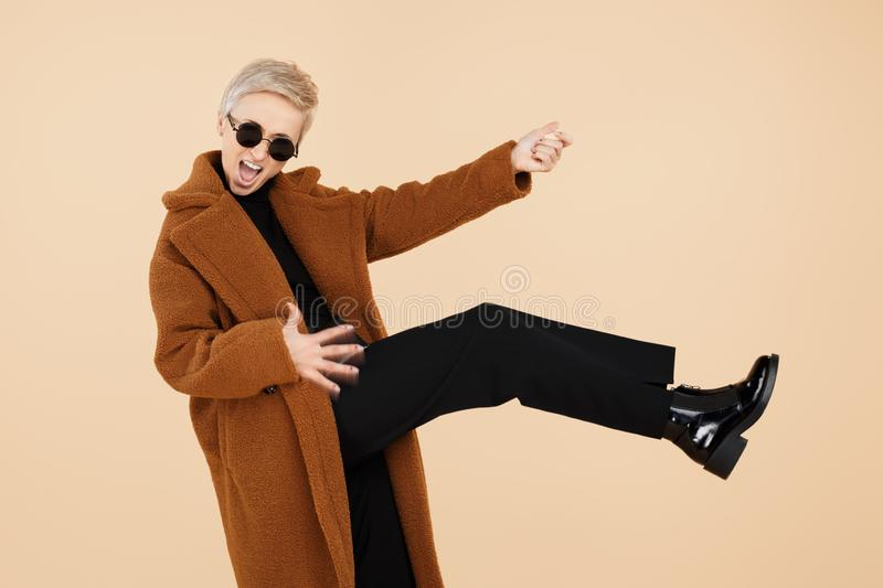 Crazy young hipster woman with blonde short hair wearing a coat and sunglasses play on invisible guitar isolated over royalty free stock photos