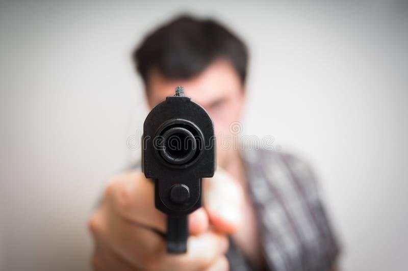 Crazy young man aiming gun at you royalty free stock images