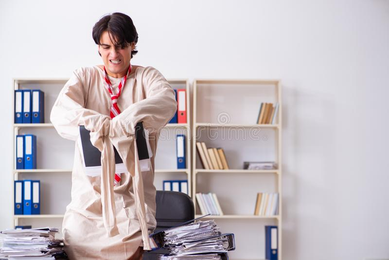 The crazy young man in straitjacket at the office stock photography