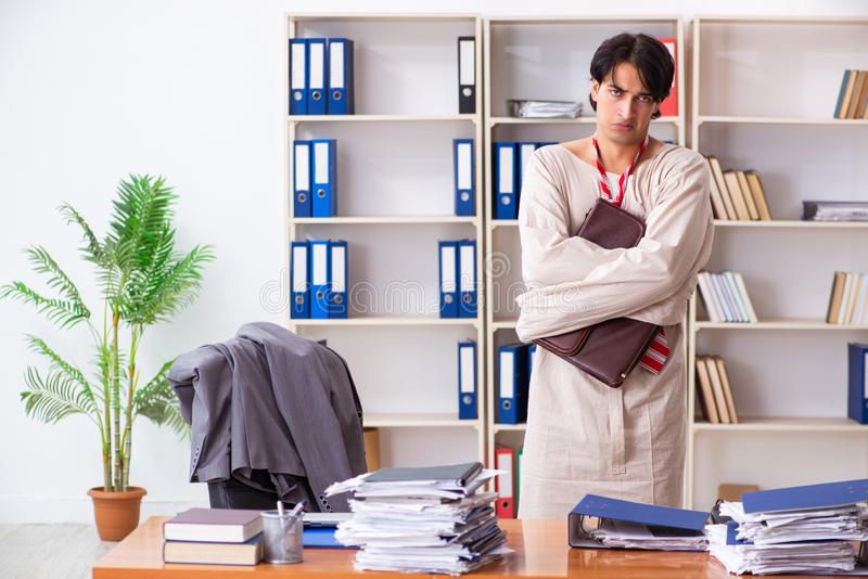 Crazy young man in straitjacket at the office stock photos