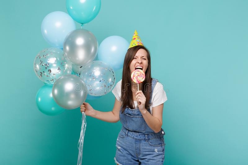 Crazy young woman in denim clothes, birthday hat biting round lollipop celebrating holding colorful air balloons. Isolated on blue turquoise background royalty free stock images