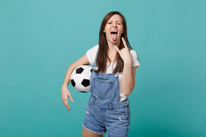 Crazy young woman football fan cheer up support favorite team with soccer ball showing tongue, horns up gesture isolated. On blue turquoise background. People stock photo