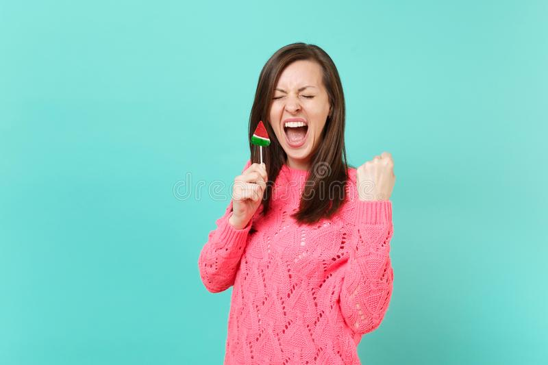 Crazy young woman in knitted pink sweater with closed eyes screaming, doing winner gesture, hold in hand watermelon stock images