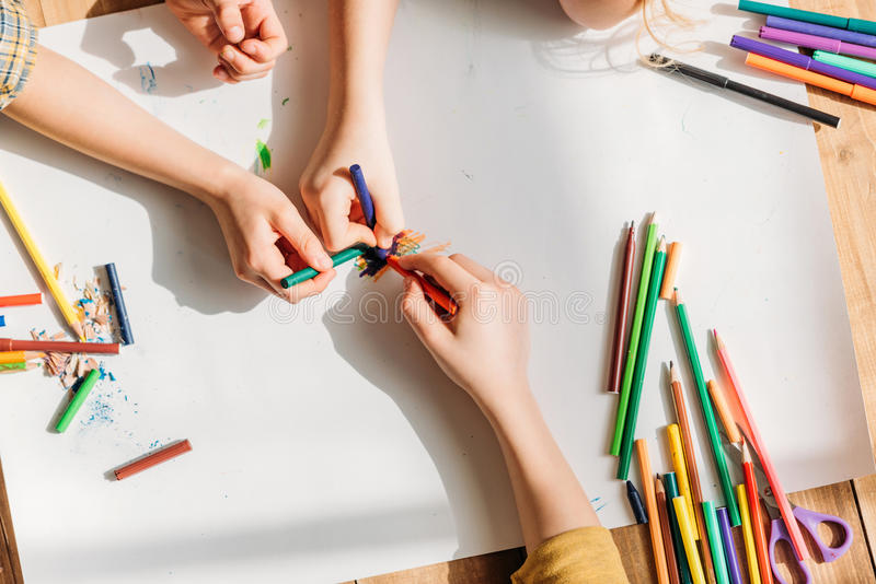 Crcute kids drawing on paper with pencils while lying on floor stock photo