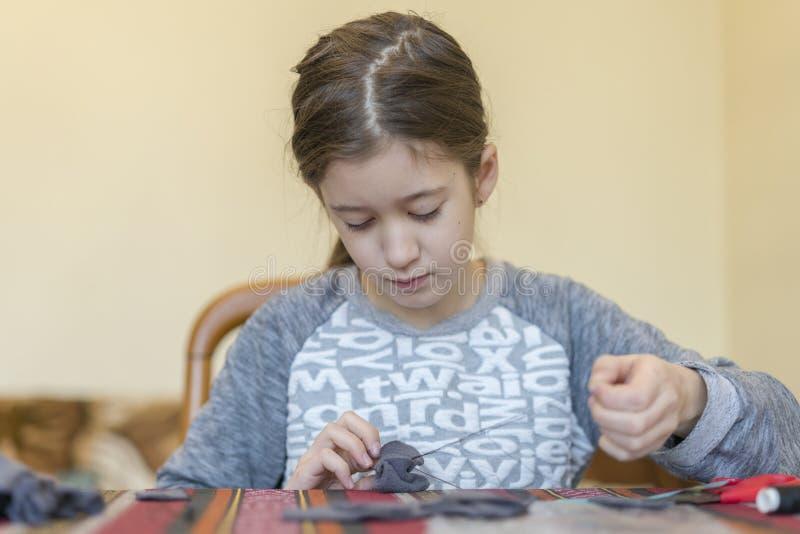 creación la niña cose el juguete hecho del fieltro La niña cose un ratón gris La niña cose un juguete imagen de archivo