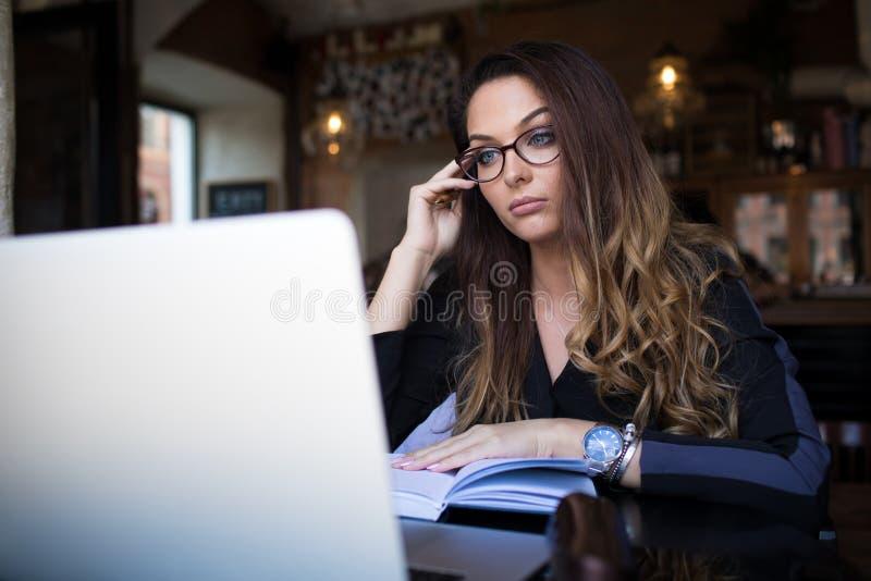 Creador contento femenino hermoso que trabaja en la página web vía el dispositivo del cuaderno imágenes de archivo libres de regalías