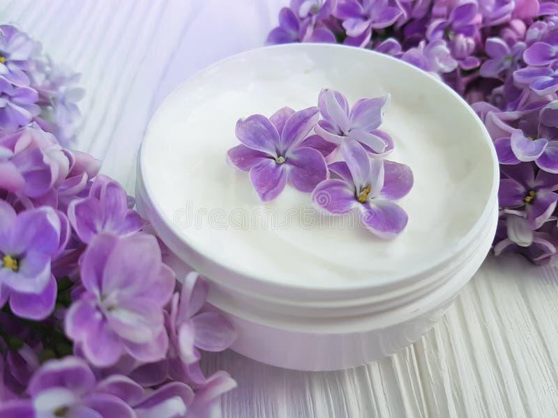 Cream косметическая бутылка сирени увлажнителя цветка на белое деревянном стоковое фото rf
